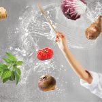 Köchin mit Taktstock und alten Obst,- Gemüse,- Kräutersorten