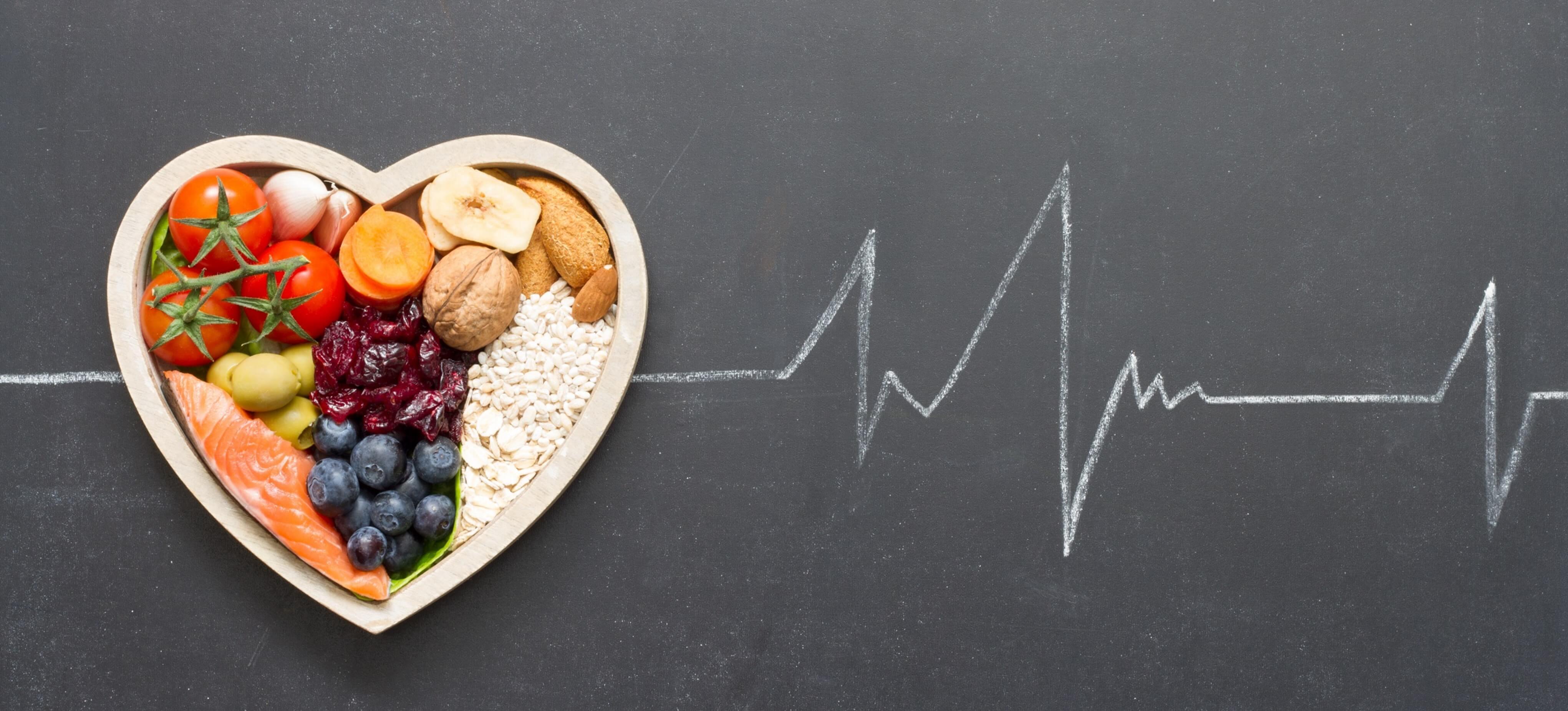 Herz mit gesunden, mediterranen Lebensmitteln und Herzlinie auf Tafel