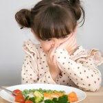 Kind sitzt vor Teller mit Gemüse und verzieht das Gesicht