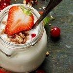 Joghurt im Glas dekoriert mit verschiedenen Beeren und Haferflocken