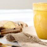 EinGlas goldene Milch mit Gewürzen auf hellem Tisch