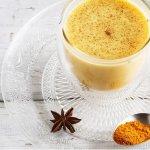 Glas mit goldener Milch, Untertasse und einem Teelöffel Kurkuma