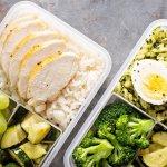 Vorkochen - ein Reis- und ein Nudelgericht in Tupperware portioniert mit verschiedenem Obst und Gemüse