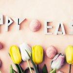 Eier, Tulpen und die Wörter Happy Easter auf einem rosa Hintergrund