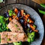 Gebratener Lachs mit Brokkoli, Zwiebeln und Karotten auf einem schwarzem Teller angerichtet