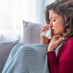 Erkältete, junge Frau sitzt mit Wolldecke auf dem Sofa und putzt sich die Nase mit einem Taschentuch.
