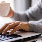 Junge Frau arbeitet am Laptop im Homeoffice mit Kaffeetasse in der Hand