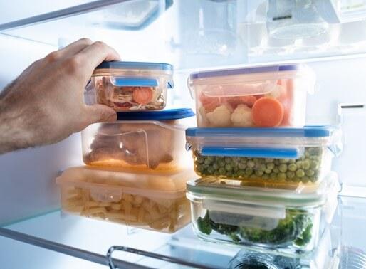 Die menschliche Hand nimmt Behälter mit gefrorenem gemischtes Gemüse aus Kühlschrank
