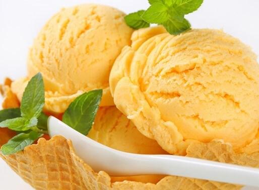Mango-Kraeuter-Eiskugeln im Waffelbecher mit Minze dekoriert
