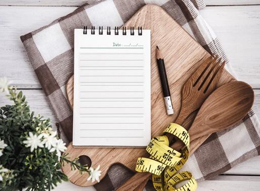 Line Notepad mit Diet-Plan Liste Text auf der Tafel mit Holzgabel Gabel und Löffel und Messband auf weißem Tisch , Rezepte oder Ernährungsplan für gesunde Gewohnheiten Aufnahme Note Hintergrund Konzept