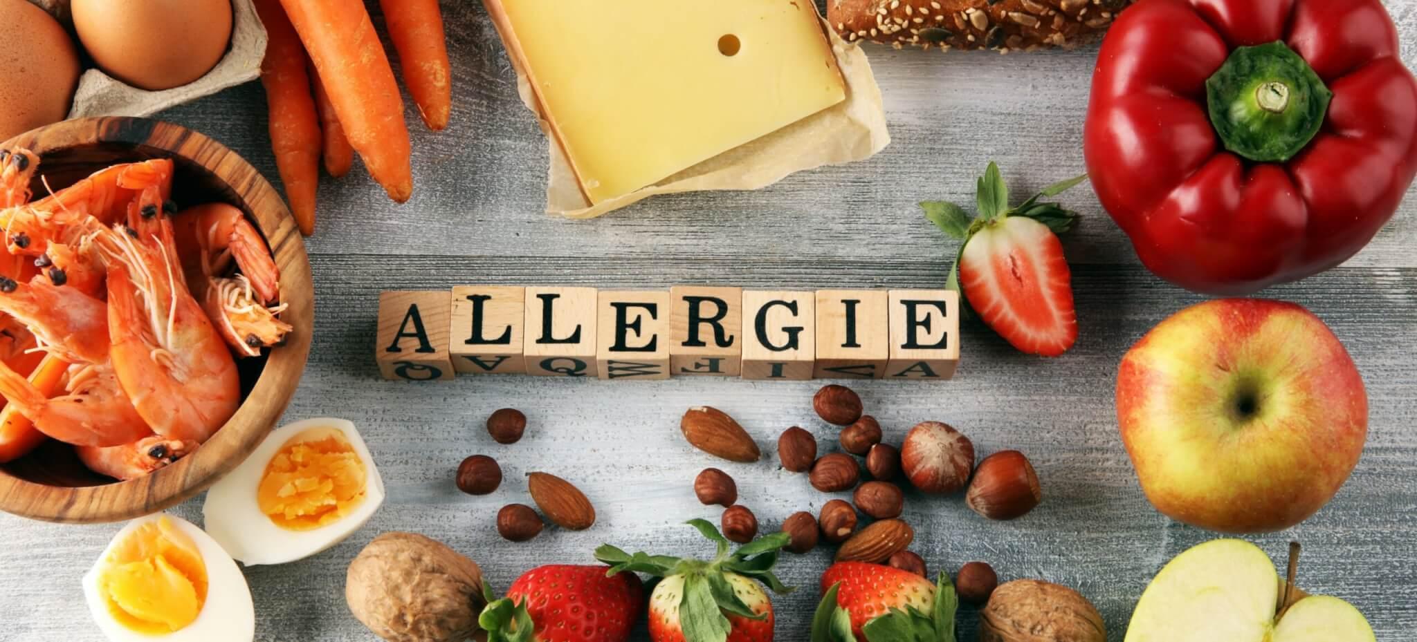 """allergieauslösende Lebensmittel wie Schalentiere, Milch, Nüsse, Erdbeeren. In der Mitte steht in Holzbuchstaben """"Allergie"""""""
