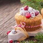 Kokos-Cranberry Muffin mit Kokosflocken und Cranberries dekoriert auf einem Holzuntergrund